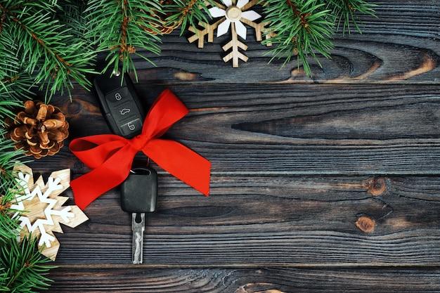 Vue rapprochée des clés de la voiture avec l'arc rouge comme présent sur fond vintage en bois