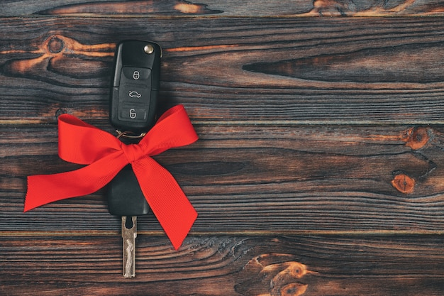 Vue rapprochée des clés de la voiture avec un arc rouge comme présent sur fond vintage en bois