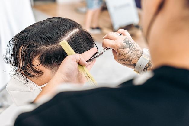 Vue rapprochée d'un coiffeur à l'aide de ciseaux pour couper les cheveux d'un jeune homme avec masque dans un salon