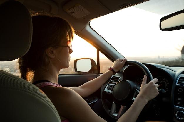 Vue rapprochée d'une conductrice tenant le volant au volant d'une voiture au coucher du soleil.