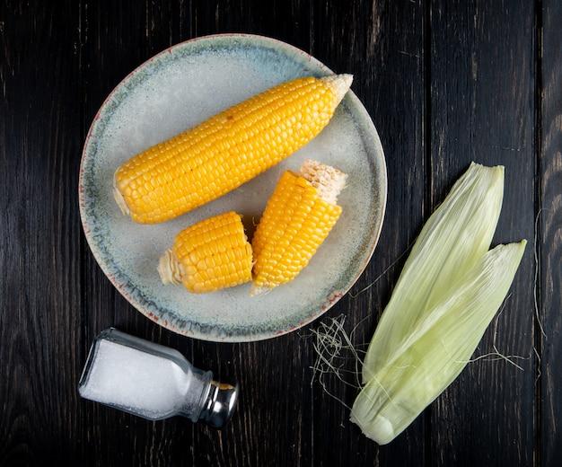 Vue rapprochée des cors entiers et coupés cuits dans une assiette avec de la coque de maïs et du sel sur la surface noire