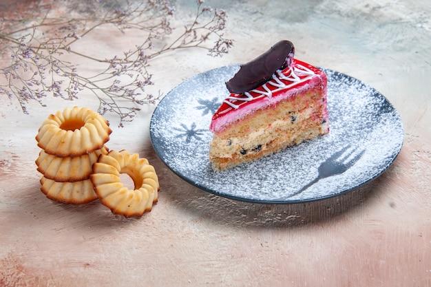 Vue rapprochée de côté une assiette de gâteau de gâteau avec des biscuits au chocolat