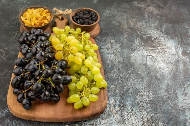 Vue rapprochée de côté fruits grappes de raisins verts et noirs sur le plateau bols de fruits secs