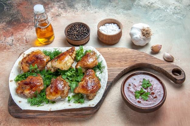 Vue rapprochée de côté huile de poulet sauce à l'ail épices poulet aux herbes sur lavash sur la carte
