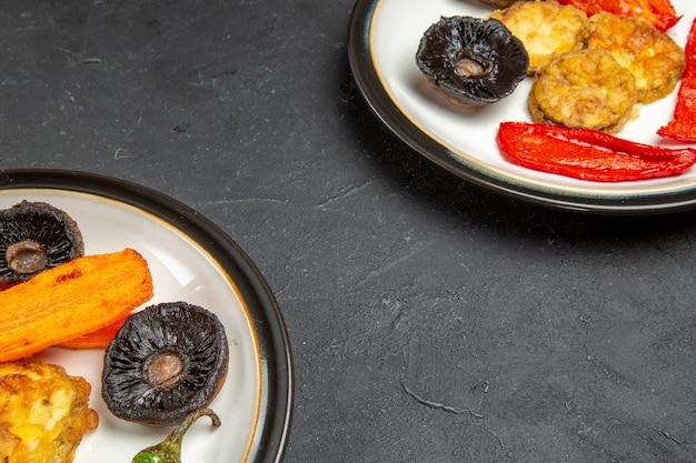 Vue rapprochée de côté légumes légumes rôtis sur les assiettes sur la table