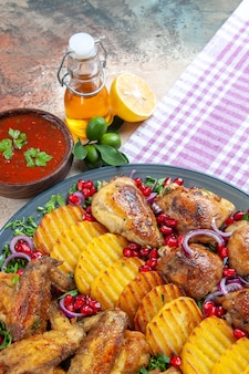 Vue rapprochée de côté poulet les pommes de terre appétissantes ailes de poulet herbes sauce oignon bouteille d'huile