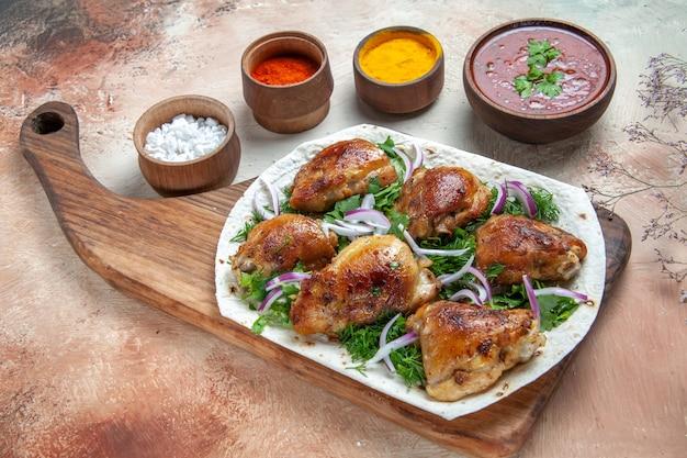 Vue rapprochée de côté poulet poulet aux herbes sur des bols de sauce lavash et épices colorées
