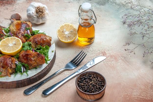 Vue rapprochée de côté poulet poulet aux herbes sur le plateau fourchette couteau ail huile citron