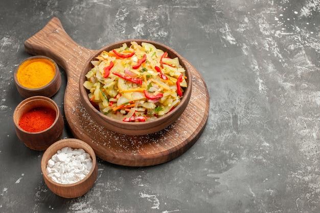 Vue rapprochée de côté salade trois types de salade de légumes épices dans le bol sur la planche
