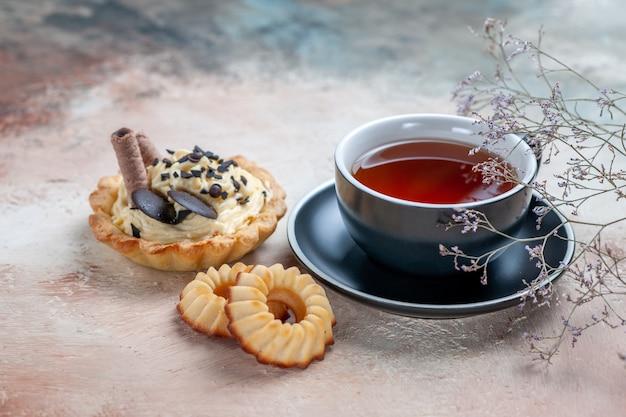 Vue rapprochée de côté une tasse de thé cupcake une tasse d'un appétissant biscuits au thé