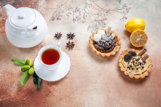 Vue rapprochée de côté une tasse de thé une tasse de thé théière au citron cupcakes
