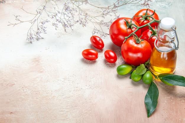 Vue rapprochée de côté tomates bouteille d'agrumes d'huile avec des feuilles de tomates avec pédicelles