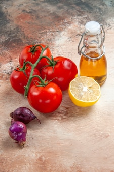 Vue rapprochée de côté tomates bouteille d'huile tomates oignons citron sur la table