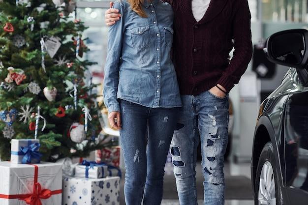 Vue rapprochée d'un couple charmant qui se tient près de la voiture et de l'arbre de noël au moment du nouvel an