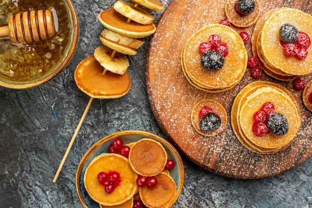 Vue rapprochée de crêpes américaines sur planche à découper et miel avec cuillère sur table grise
