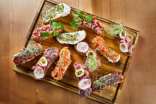 Vue rapprochée sur une délicieuse bruschetta assortie de saumon, de boeuf et de tomates sur une surface en bois