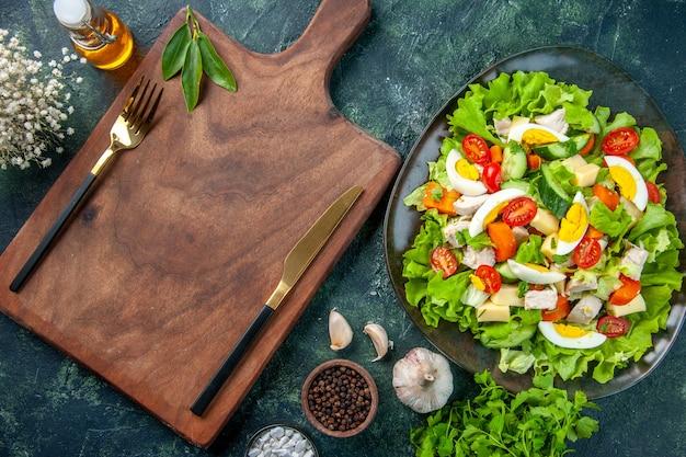Vue rapprochée de la délicieuse salade avec de nombreux ingrédients frais épices bouteille d'huile couverts ail mis sur planche à découper en bois