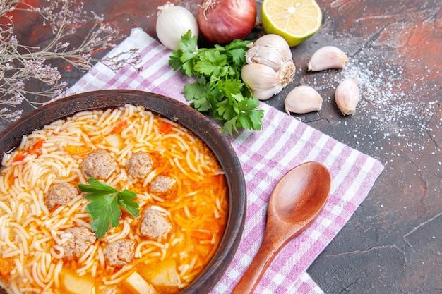 Vue rapprochée d'une délicieuse soupe au poulet avec des nouilles vertes et une cuillère sur une serviette rose bouteille d'huile d'ail citron sur fond sombre