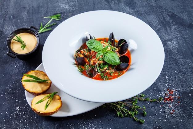 Vue rapprochée sur une délicieuse soupe de fruits de mer dans un bol de restaurant blanc. bouillabaisse aux moules, saumon et basilic avec une collation de pommes de terre à la sauce au fromage. fond sombre. photo de nourriture pour le menu ou la recette