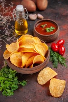 Vue rapprochée de délicieuses chips croustillantes de pommes de terre faites maison dans un petit bol marron bouteille d'huile de pommes de terre tomates vertes ail et ketchup sur fond sombre