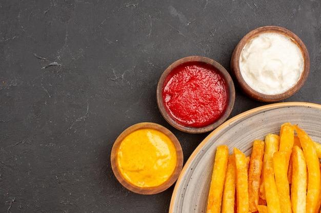 Vue rapprochée de délicieuses frites avec des assaisonnements sur un espace sombre