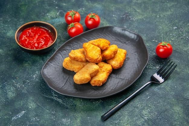 Vue rapprochée de délicieuses pépites de poulet dans une fourchette de tomates en assiette noire sur une surface sombre avec un espace libre
