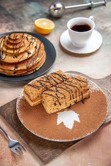 Vue rapprochée de délicieux desserts et une tasse de thé au citron et cannelle sur table colorée