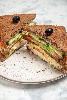 Vue rapprochée d'un délicieux sandwich avec du pain noir décoré d'olive sur une assiette sur une surface blanche tachée