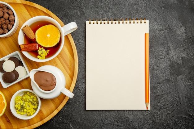 Vue rapprochée de dessus des bonbons sur un cahier de table avec un crayon jaune à côté de l'assiette de baies de chocolat, des bâtons de cannelle au citron et une tasse de thé au citron