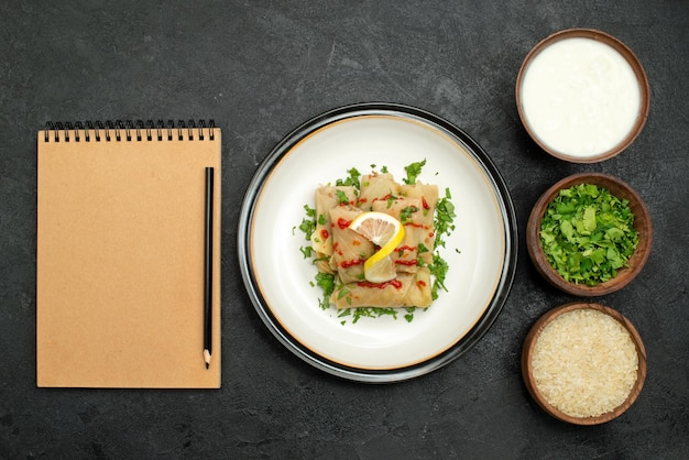 Vue rapprochée de dessus chou farci chou farci aux herbes citron et sauce sur assiette blanche et riz aux herbes et crème sure dans des assiettes à côté d'un cahier crème et d'un crayon sur un tableau noir
