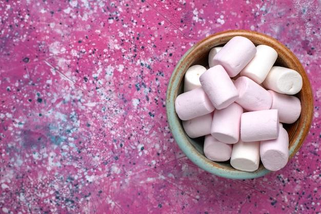 Vue rapprochée de dessus de délicieuses guimauves sucrées peu formées à l'intérieur d'un pot rond sur un bureau rose.