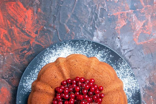 Vue rapprochée de dessus un délicieux gâteau savoureux et des groseilles rouges sur la plaque grise