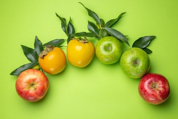 Vue rapprochée de dessus fruits colorés pommes vertes et rouges kakis avec des feuilles