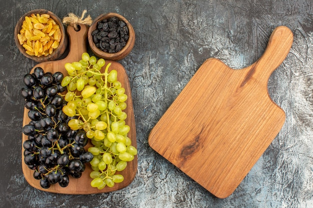 Vue rapprochée de dessus les fruits secs la planche à découper à côté des raisins et deux bols de fruits secs