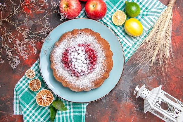Vue rapprochée de dessus un gâteau un gâteau avec des baies de sucre en poudre d'agrumes sur la nappe à carreaux