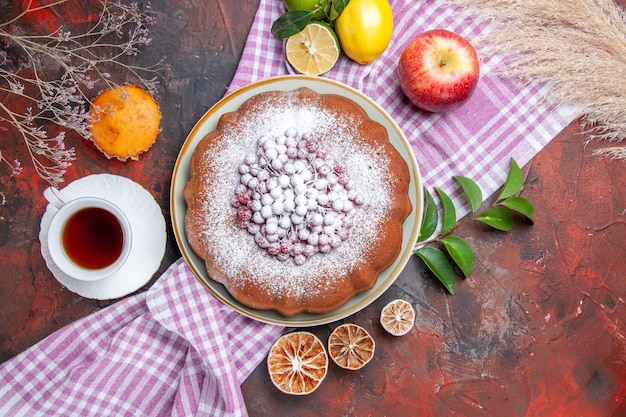 Vue rapprochée de dessus un gâteau une tasse de thé un gâteau pomme citrons avec des feuilles sur la nappe cupcake
