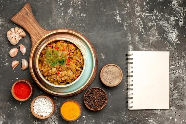 Vue rapprochée de dessus haricots verts assiette blanche des haricots verts avec des tomates sur la planche de bois cinq sortes d'épices cahier blanc et ail sur la table sombre