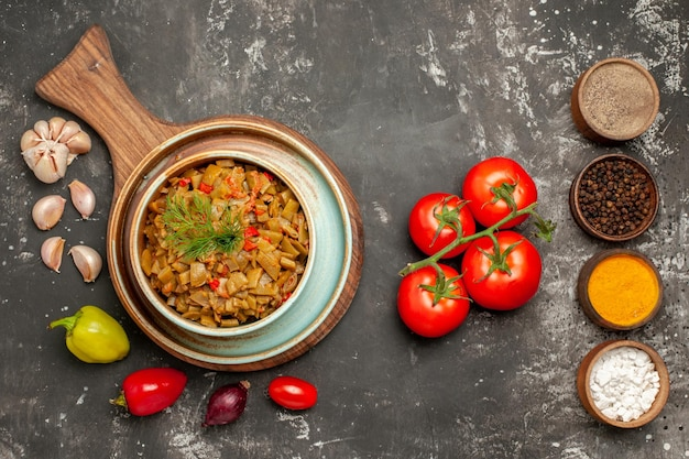 Vue rapprochée de dessus haricots verts assiette de cahier blanc des haricots verts avec tomates sur la planche poivrons oignon ail tomates avec pédicelle et épices colorées sur la table sombre