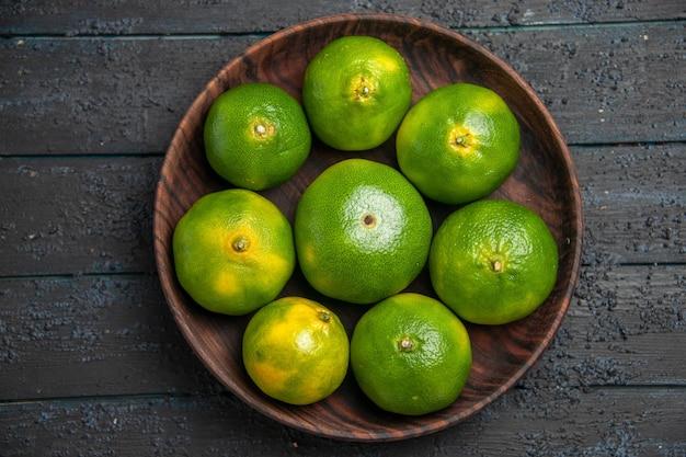 Vue rapprochée de dessus huit citrons verts dans un bol huit citrons verts dans un bol au centre d'une table grise