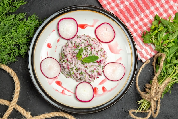 Vue rapprochée de dessus un plat un plat de corde de verts rougeâtres et la nappe à carreaux