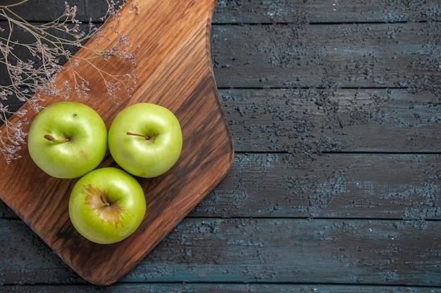 Vue rapprochée de dessus des pommes à bord de trois pommes vertes sur une planche de cuisine à côté de branches d'arbres sur le côté gauche de la table sombre
