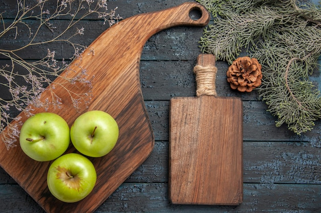 Vue rapprochée de dessus des pommes à bord de trois pommes vertes sur une planche de cuisine et une planche à découper entre des branches d'arbres avec des cônes sur une table sombre