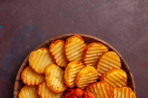 Vue rapprochée de dessus de pommes de terre au four avec des légumes cuits sur un espace sombre