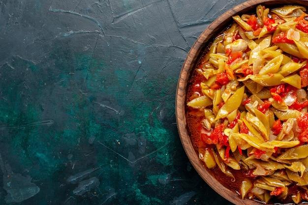 Vue rapprochée de dessus repas de légumes en tranches cuit avec différents ingrédients sur une surface bleu foncé