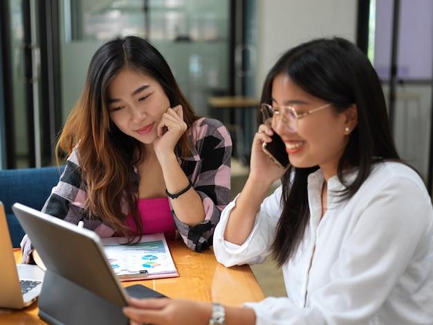 Vue rapprochée de deux étudiantes universitaires parlant au téléphone tout en faisant une mission avec son ami au café