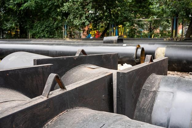 Vue rapprochée de deux nouvelles conduites d'eau isolées sur la route de la ville en journée d'été. concept d'infrastructure d'assainissement urbain, modernisation et reconstruction du système d'eau souterraine.