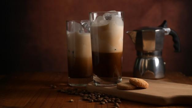 Vue rapprochée de deux verres de café glacé avec biscuit sur plateau en bois, cafetière et grains de café décorés sur table