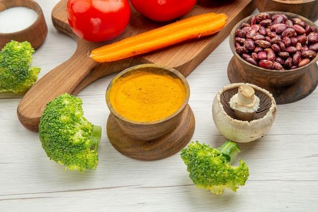 Vue rapprochée du bas de la branche de tomate sur une planche de service en bois, du sel, du curcuma, du brocoli, des haricots rouges, du bol sur une table grise