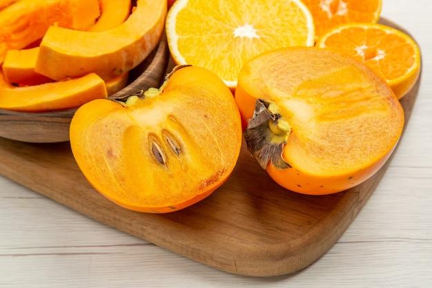 Vue rapprochée du bas de la courge musquée dans des bols coupés des kakis, des mandarines et des oranges sur une planche à découper sur un tableau blanc