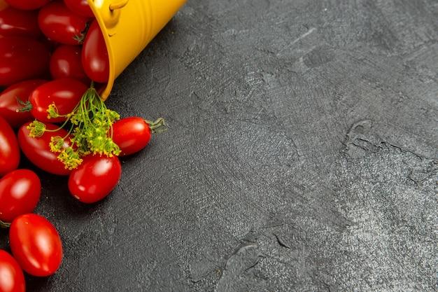 Vue rapprochée du bas renversé seau jaune rempli de tomates cerises et de fleurs d'aneth en haut à gauche du fond sombre